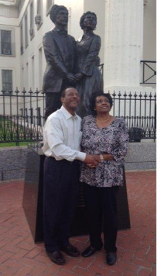 Curtis and Jannice May pose by a statue of Dred and Harriet Scott