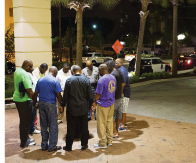 Worshipers gather to pray in a hotel parking lot across the street from the scene of the massacre. Credit: David Goldman, AP